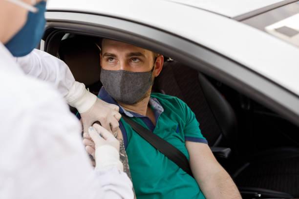 man receiving vaccine for covid-19 on car - vacina da gripe imagens e fotografias de stock