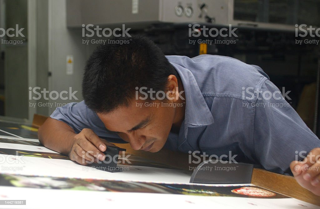 A man rechecking details on his work royalty-free stock photo