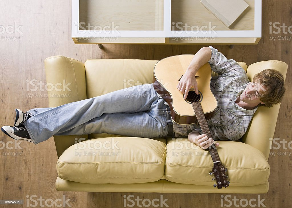 Man Reclining on Sofa Playing Guitar royalty-free stock photo