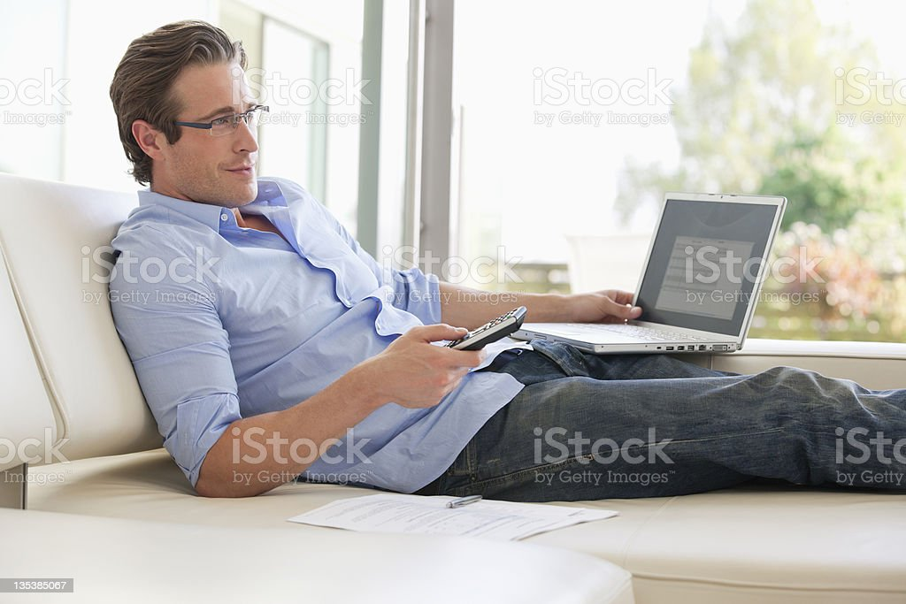 Man reclining on sofa using remote control and laptop stock photo