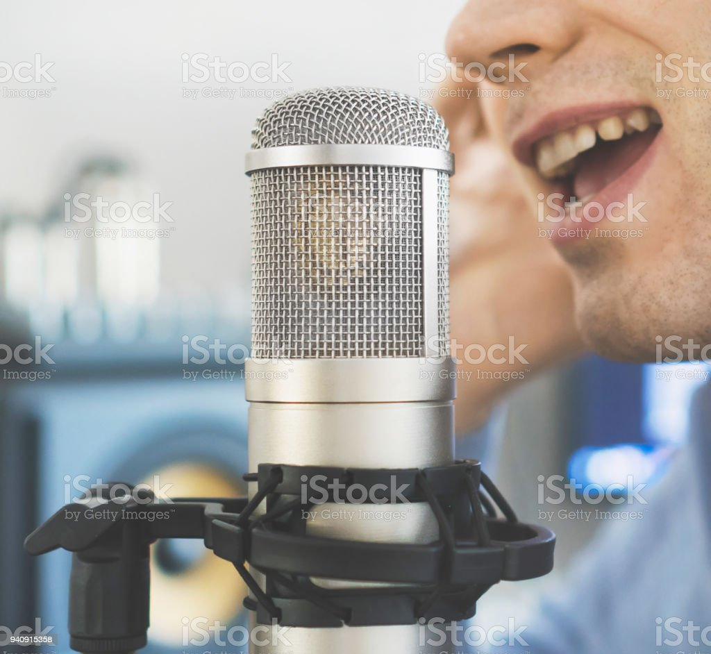 Man recording a song in record studio. stock photo