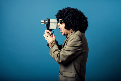 Man records a video with retro camera and looks surprised