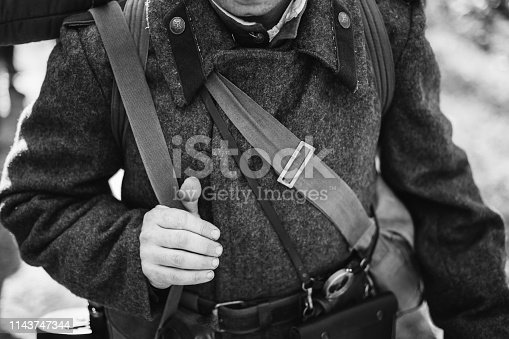 1143756392 istock photo Man Re-enactor Dressed As World War II Soviet Russian Red Army Officer Soldier. Russian Overcoat Uniform In WWII WW2 Times. Photo In Black And White Colors 1143747344
