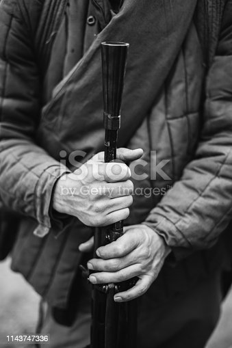 1061204700 istock photo Man Re-enactor Dressed As World War II Soviet Russian Red Army Soldier Holding World War II Weapon Degtyaryov DP Machine Gun. WWII WW2 Russian Ammunition. Photo In Black And White Colors 1143747336