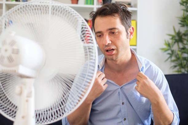 Mann mit Elektrolüfter gegen Hitzewelle im Sommer erfrischend – Foto
