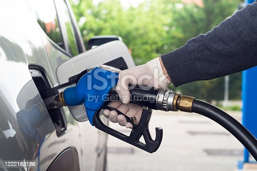 Man refueling car wearing protective latex gloves to prevent infections.