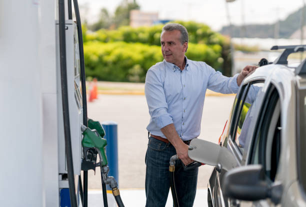 Man refueling his car at a gas station stock photo