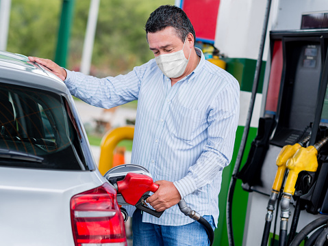 Man refueling his car at the gas station wearing a facemask during the COVID-19 pandemic