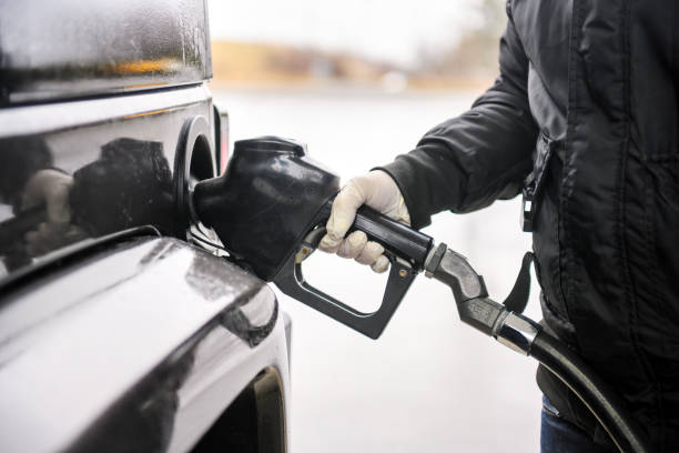 man refueling the car, wearing protective gloves because of coronavirus - covid stock pictures, royalty-free photos & images