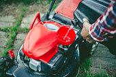 Man refuelling a lawn mower in his back yard