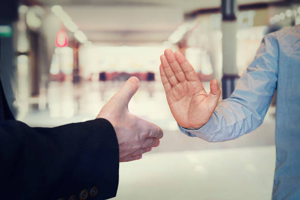 man refusing hand shake with her friend to protect herself from coronavirus in public areas. Prevention of fight against pandemic. Non-contact greeting. Quarantine methods control spread of virus. stock photo