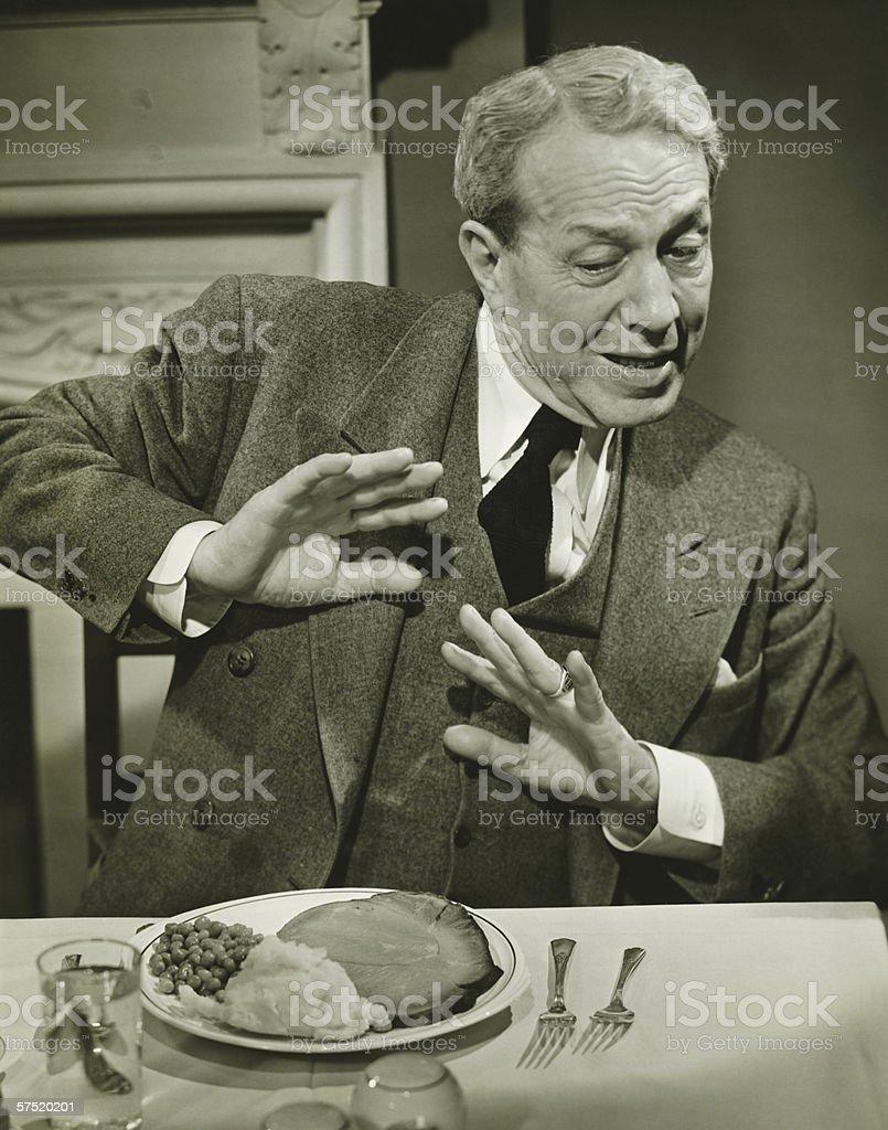 Man refusing to eat dinner in restaurant, (B&W) stock photo