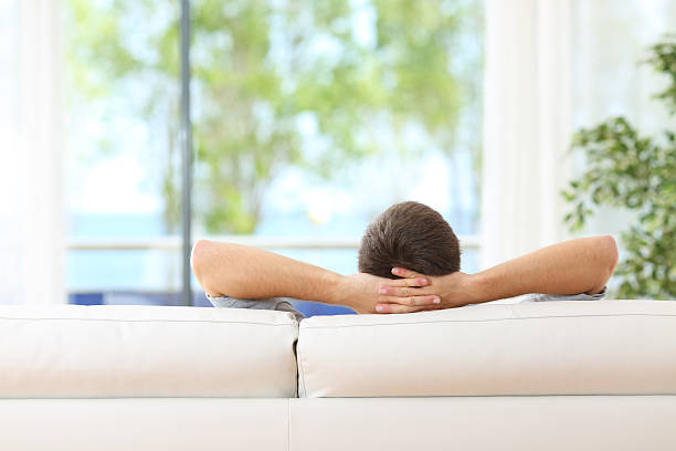 Man relaxed on a couch at home stock photo