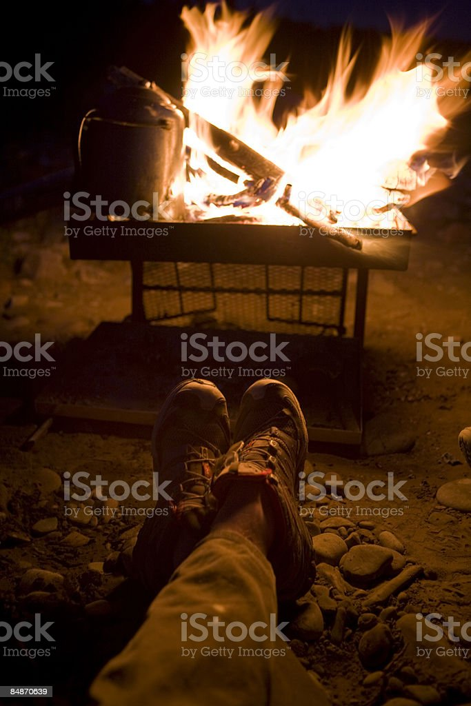 A man relaxes by a campfire. royalty-free stock photo