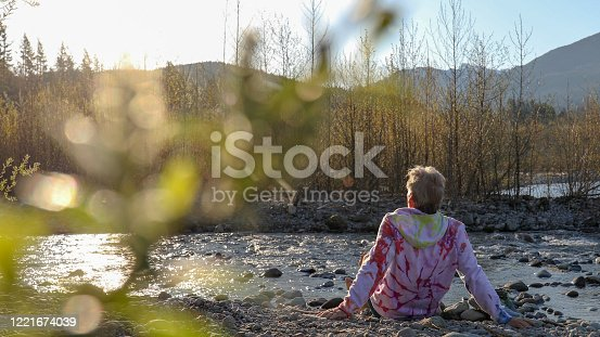 621898406 istock photo Man relaxes by riverbank in the morning 1221674039