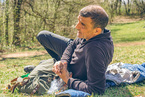Man relaxes in grassy meadow after hike and enjoys picnic