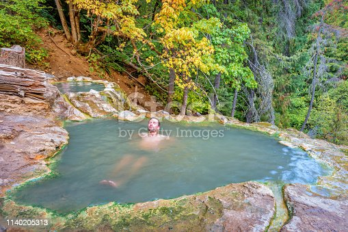Stock photograph of man relaxing in Umpqua Hot Springs in a natural setting in Umpqua National Forest, Oregon, USA.