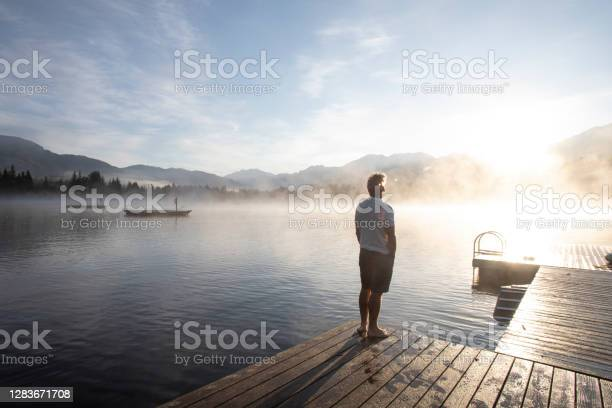 Photo of Man relaxes on lakeside dock at sunrise