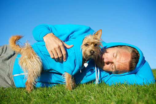 Man Relaxes with Best Friend Dog in Matching Blue Hoodies