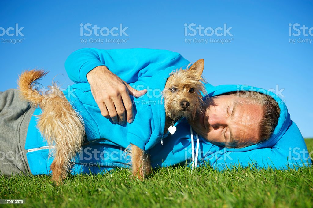 Man Relaxes with Best Friend Dog in Matching Blue Hoodies stock photo