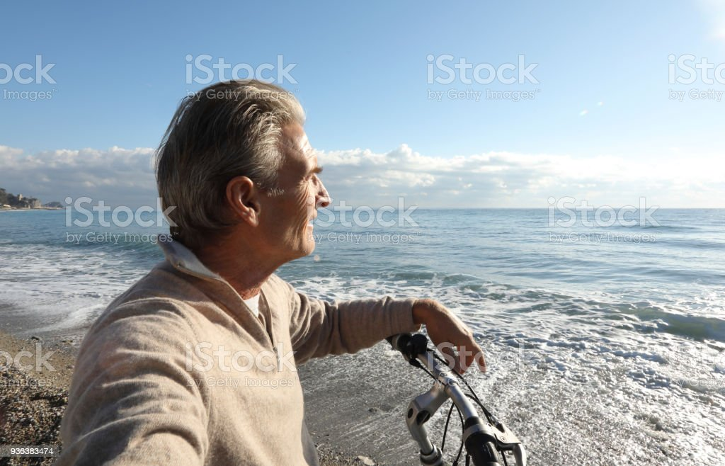 Man relaxes with bike, at beach stock photo