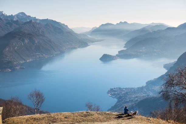 man ontspannen en genieten van uitzicht op het meer - como italië stockfoto's en -beelden