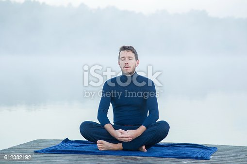 873786782 istock photo Man relaxing and meditating in the mist on the lake. 612382192