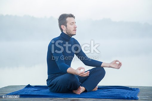 873786782 istock photo Man relaxing and practicing yoga in the mis. Foggy air. 612383362