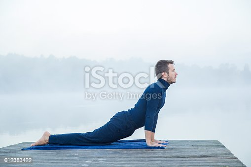 873786782 istock photo Man relaxing and practicing yoga in the mis. Foggy air. 612383422
