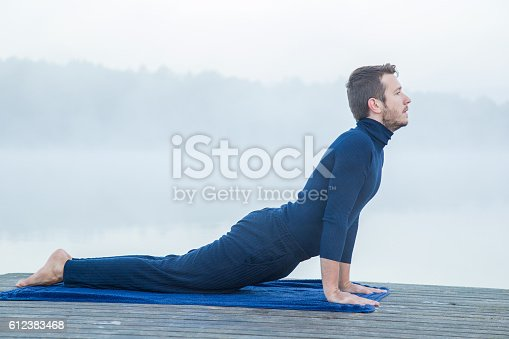873786782 istock photo Man relaxing and practicing yoga in the mis. Foggy air. 612383468