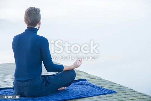 873786782 istock photo Man relaxing and practicing yoga in the mis. Foggy air. 612383610
