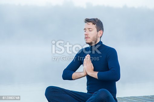 873786782 istock photo Man relaxing and practicing yoga in the mis. Foggy air. 612383748