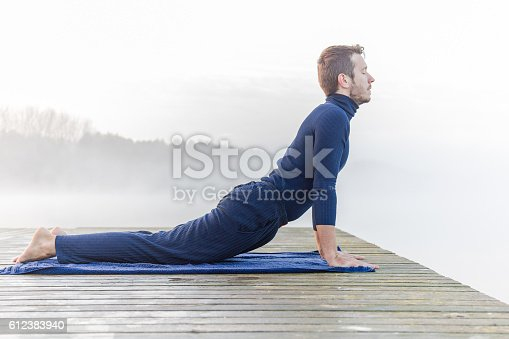 873786782 istock photo Man relaxing and practicing yoga in the mis. Foggy air. 612383940