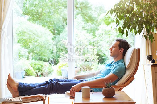 happy man relaxing in deck chair at home, wellbeing background, relaxation