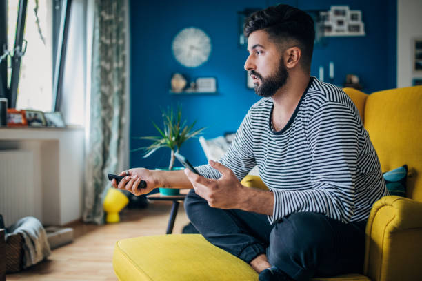 Man relaxing at home Man sitting home in his armchair, using phone and changing channels man cave stock pictures, royalty-free photos & images