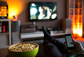 istock Man relaxing at home watching tv and eating popcorn and surfing internet 1216171041