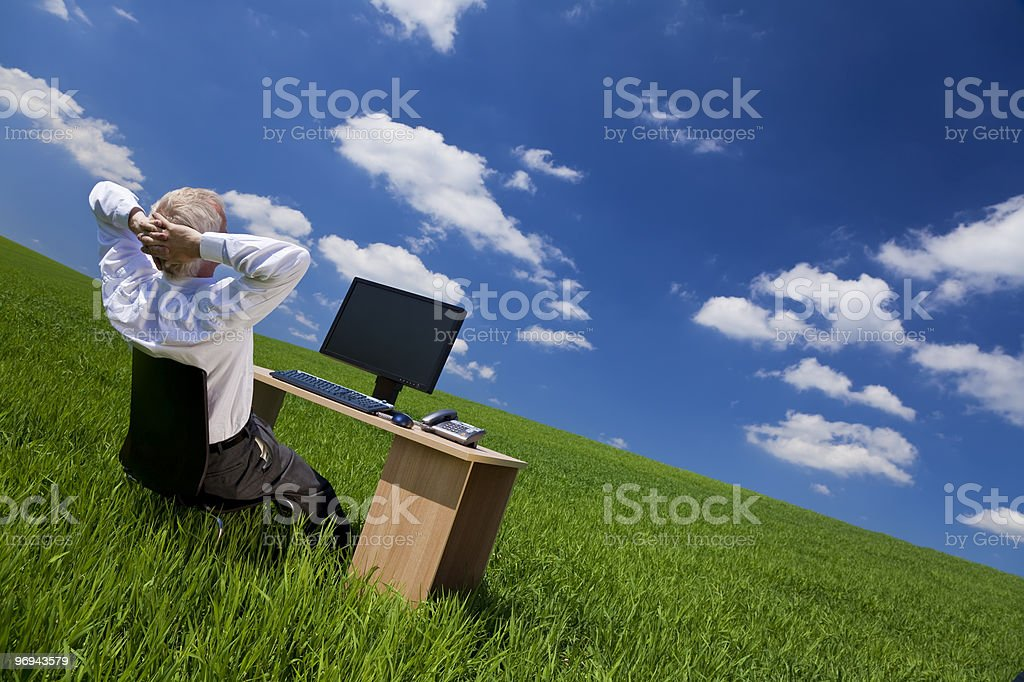 Man Relaxing At Office Desk In a Green Field royalty-free stock photo