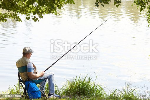 483319252 istock photo Man relaxing at the lakeside 1168992968