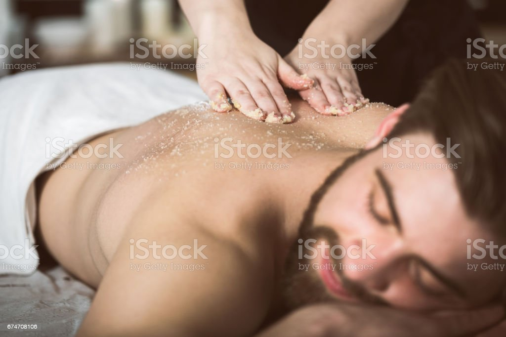 Man relaxing during a salt scrub beauty therapy stock photo