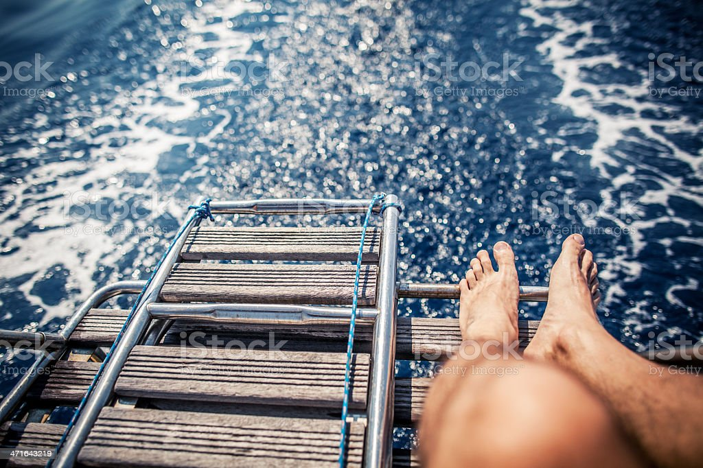Man relaxing during cruise on a Sailing Boat Man  feet, relaxing during a cruise on a Sailing Boat  Adult Stock Photo