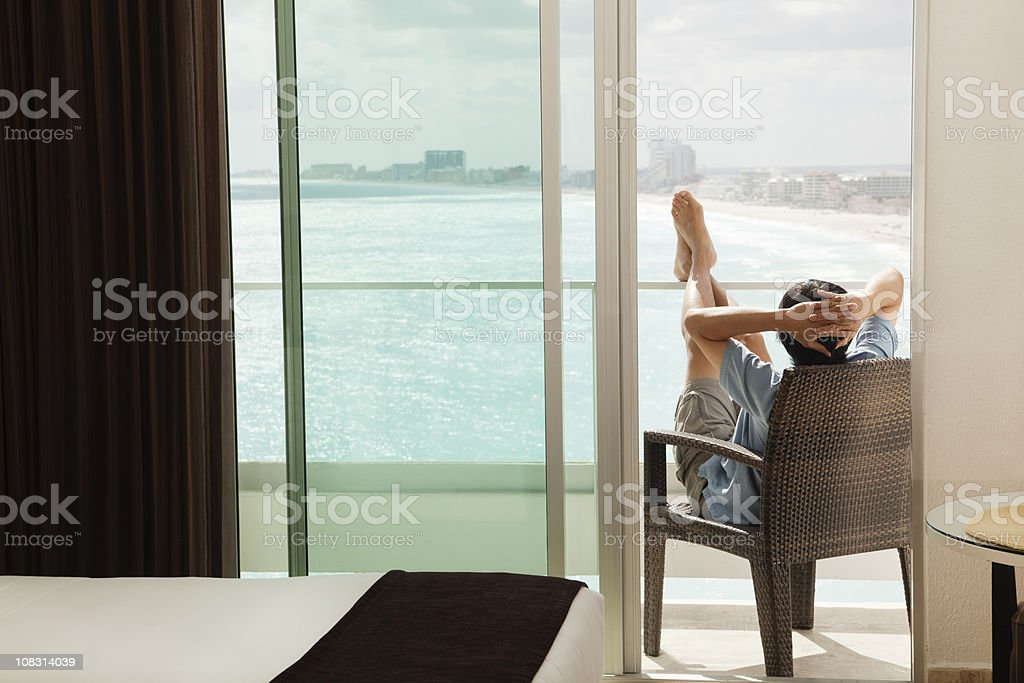 Man Relaxing, Enjoying Hotel Balcony Sea View on Beach Vacation stock photo