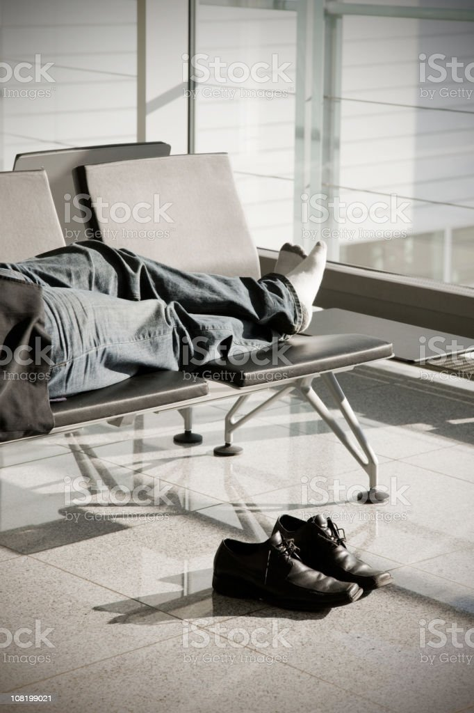 Man Relaxing Feet in Airport Waiting Area with Shoes Off royalty-free stock photo