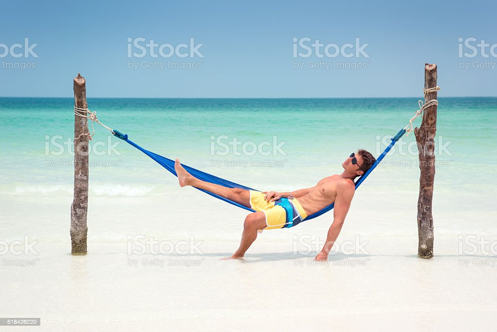 Man relaxing in a Hammock on a Tropical Island stock photo
