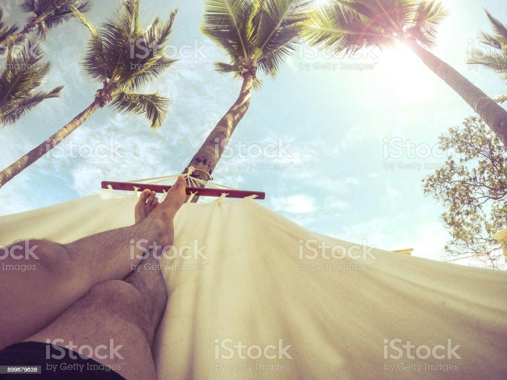 Mann in einer Hängematte unter Palmen entspannen – Foto