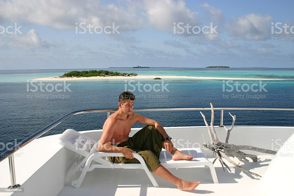 Man relaxing in a lounge chair on the cruise boat royalty-free stock photo