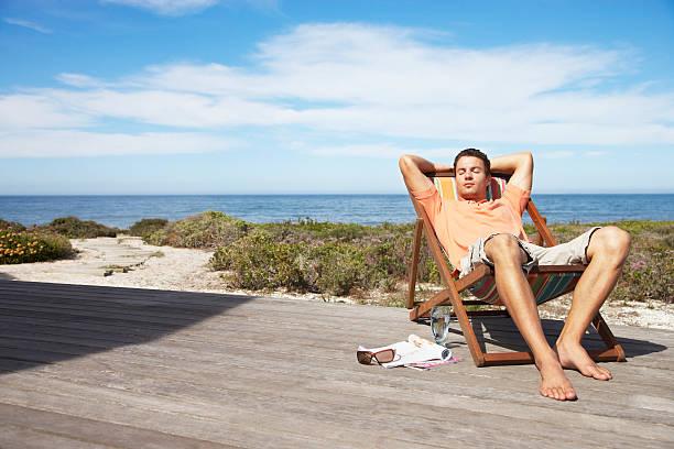 mann entspannen in einem lounge-sessel - sun chair stock-fotos und bilder
