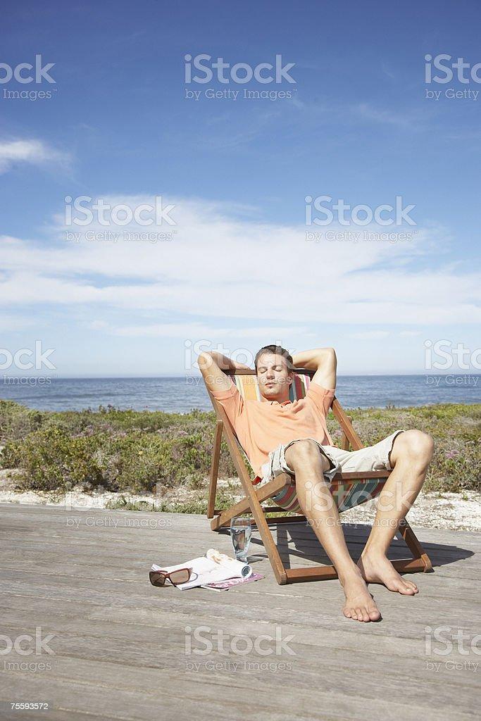 Homem relaxando em uma espreguiçadeira - foto de acervo