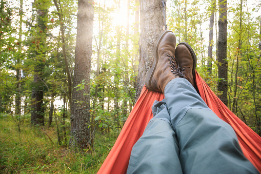 Person wearing trekking pants and hiking boots relaxing laying in camping hammock overlooking summer forest at sunset