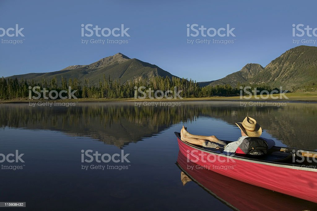 Man Relaxing in Canoe with Mountain View stock photo
