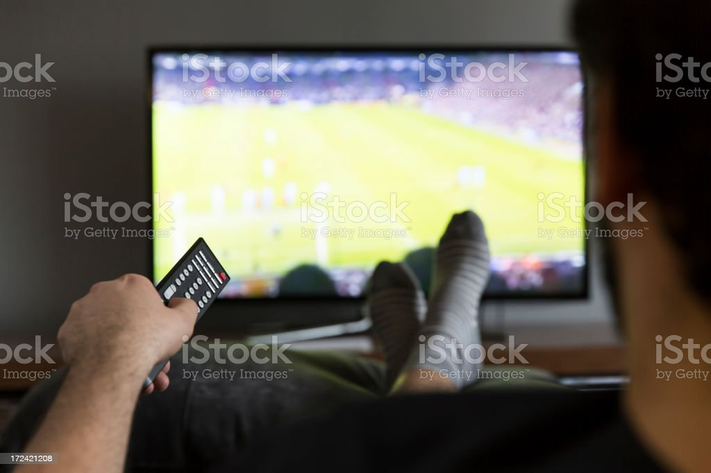 Man relaxing in couch watching soccer game royalty-free stock photo
